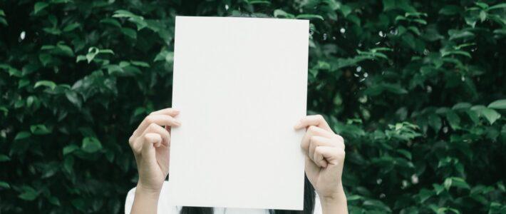 kobieta zasłaniająca twarz kartką papieru
